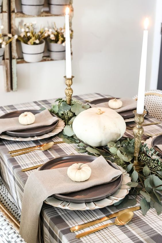 a stylish low-key fall party tablescape with a plaid tablecloth, eucalyptus, tall candles and gold cutlery