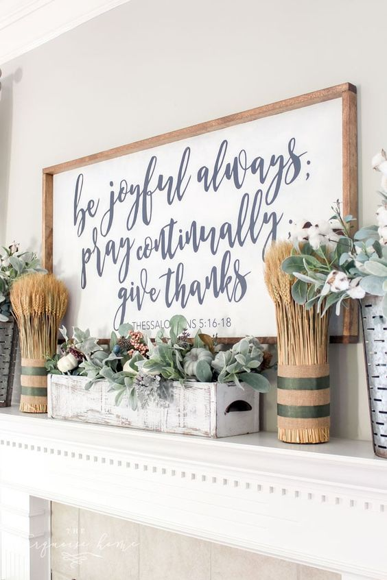 a stylish modern farmhouse mantel with wheat arrangements, a large sign, a whitewashed box with pale greenery and berries