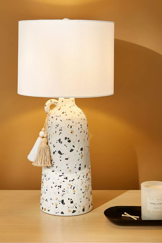 a stylish terrazzo vase table lamp with a sleek white lampshade and tassels is a cool accent idea