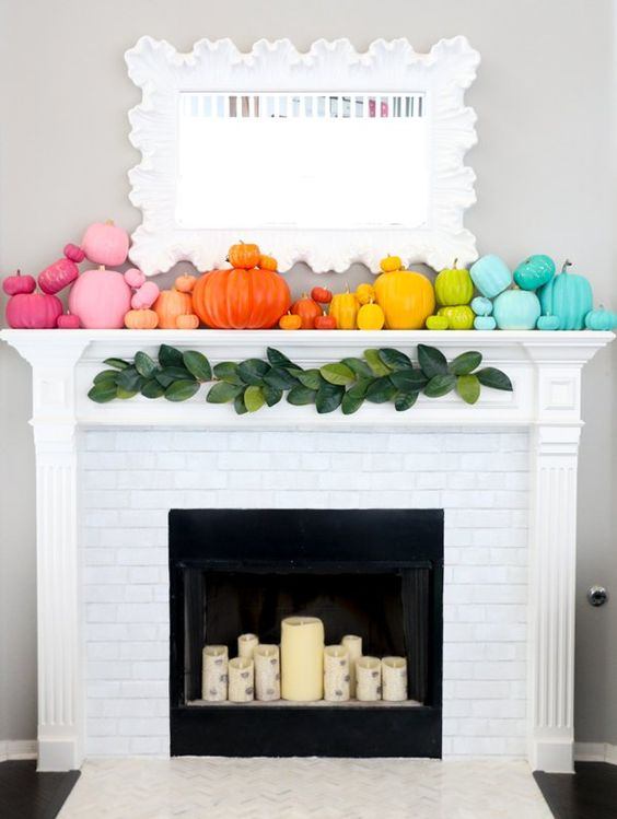 a super colorful fall mantel with super bright pumpkins and birch-inspried candles in the fireplace
