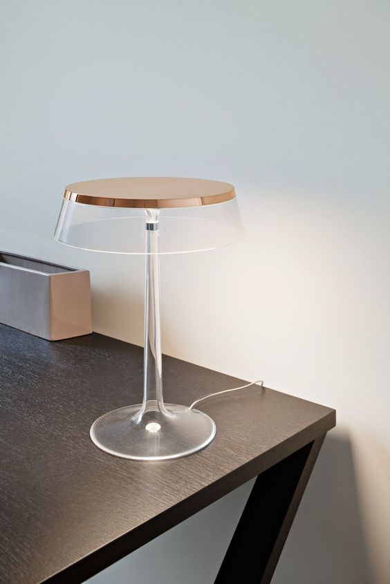 a super elegant and ultra-minimalist clear and copper table lamp with a flat lmpshade is very stylish and bold