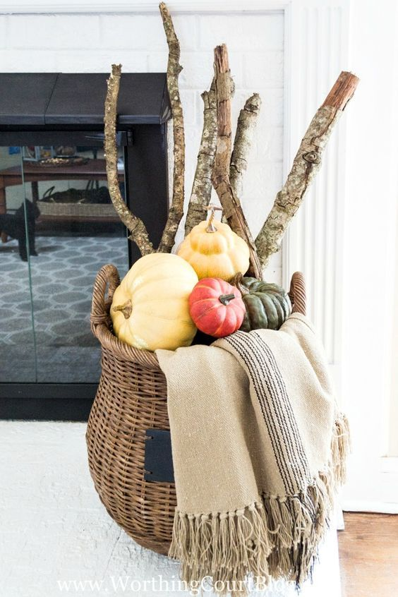 a tall basket filled with heirloom pumpkins and tree branches plus a blanket for fireplace decor