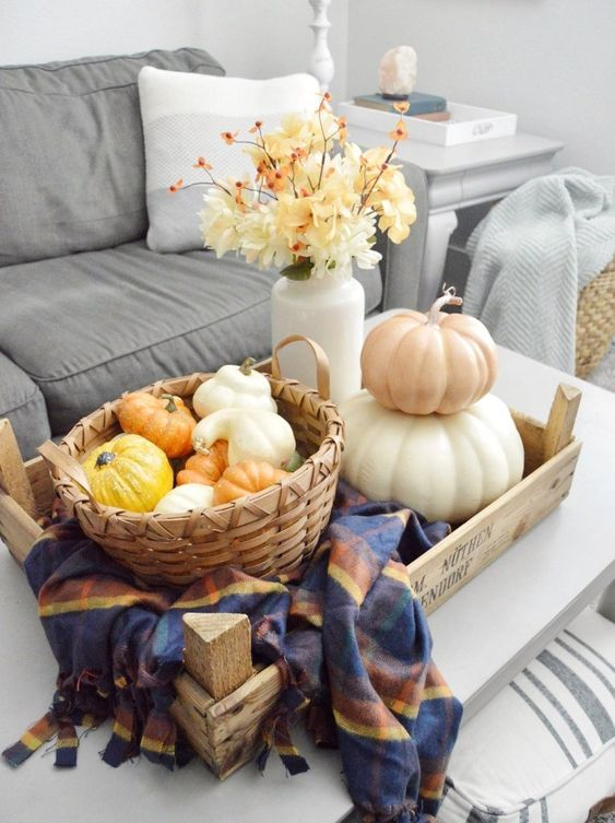a tray with a checked napkin, a basket with faux gourds and pumpkins, a stack of pumpkins and a white vase with fall blooms