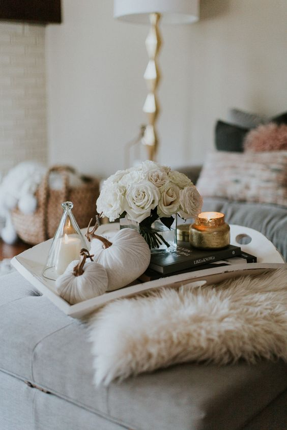a tray with a stack fo books, a candle, white fabric pumpkins and a white rose arrangement for a touch of glam