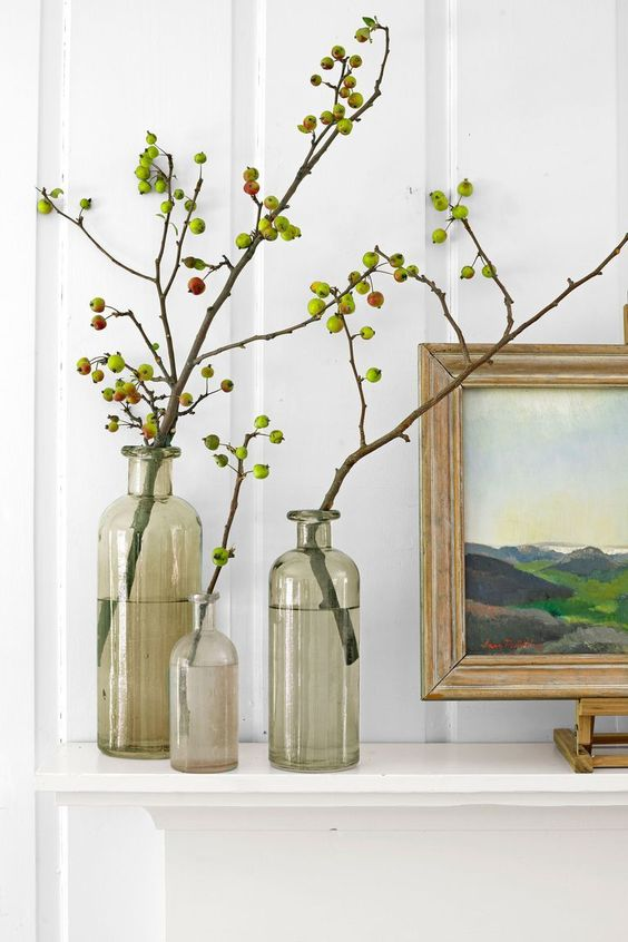 a trio of grey clear vases with branches and little apples on them