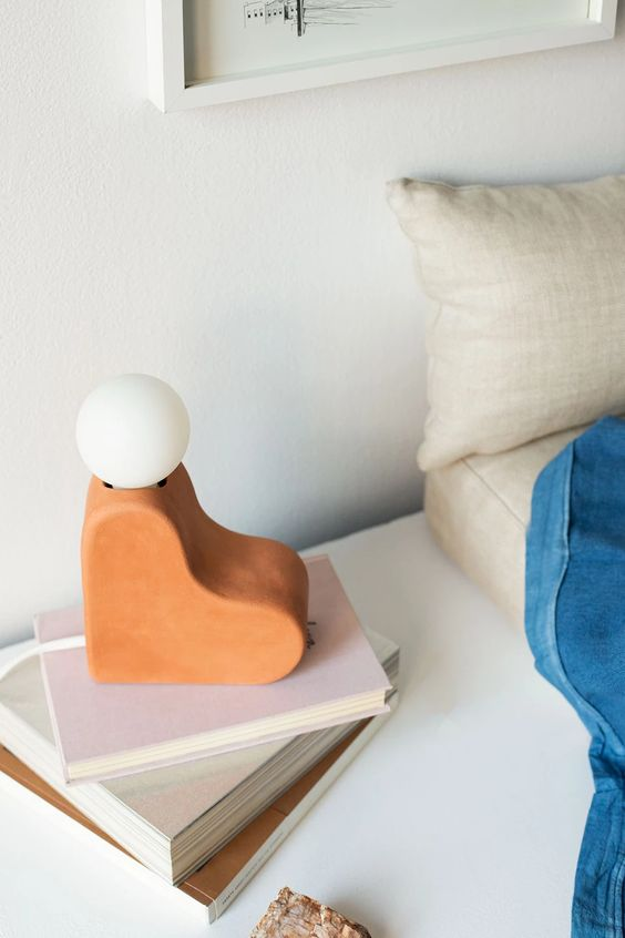 a unique terra cotta heart table lamp with a bulb on top is a creative and fun idea for a mid-century modern space