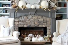 a vintage rustic mantel with fake berries, white pumpkins, a dough bowl with white pumpkins, leaves and berries
