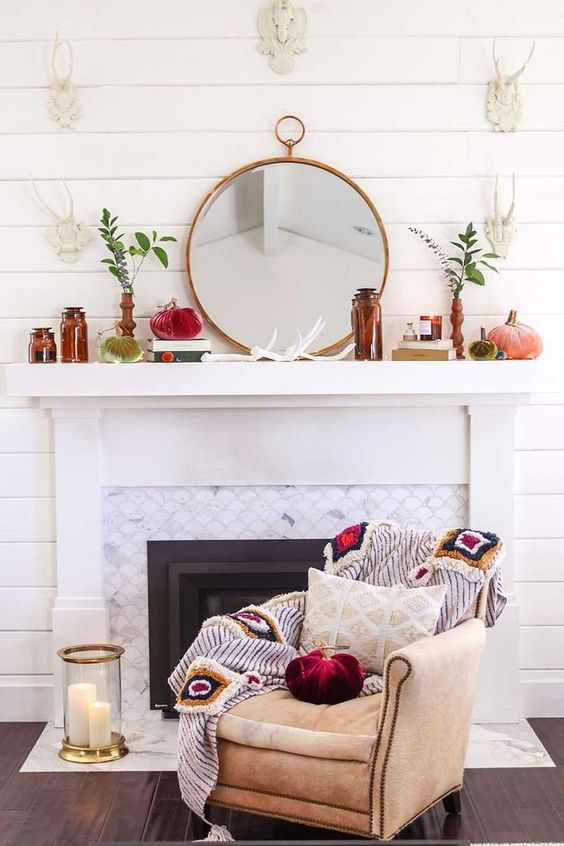 a whimsy flal mantel with brown bottles, a round mirror, greenery in vases, velvet pumpkins