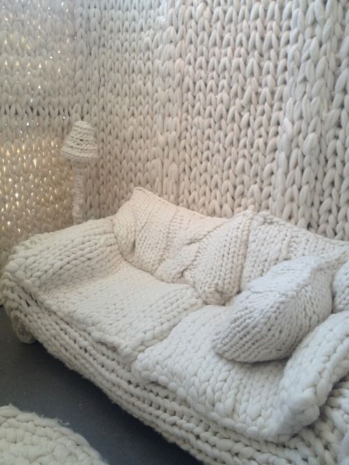 a white chunky knit sofa with matching pillows invites to relax and sleep on it