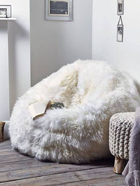a white faux fur beanbag chair plus some cozy chunky knit stools are welcoming and cozy furniture for any space
