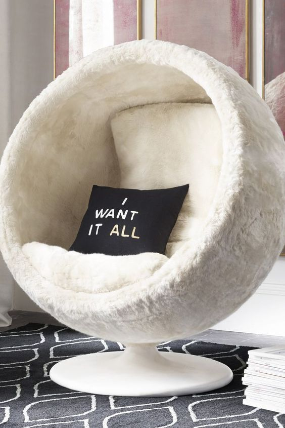 a white faux fur pod chair with cushions and pillows is a fantastic piece to dive in and enjoy comfort and coziness