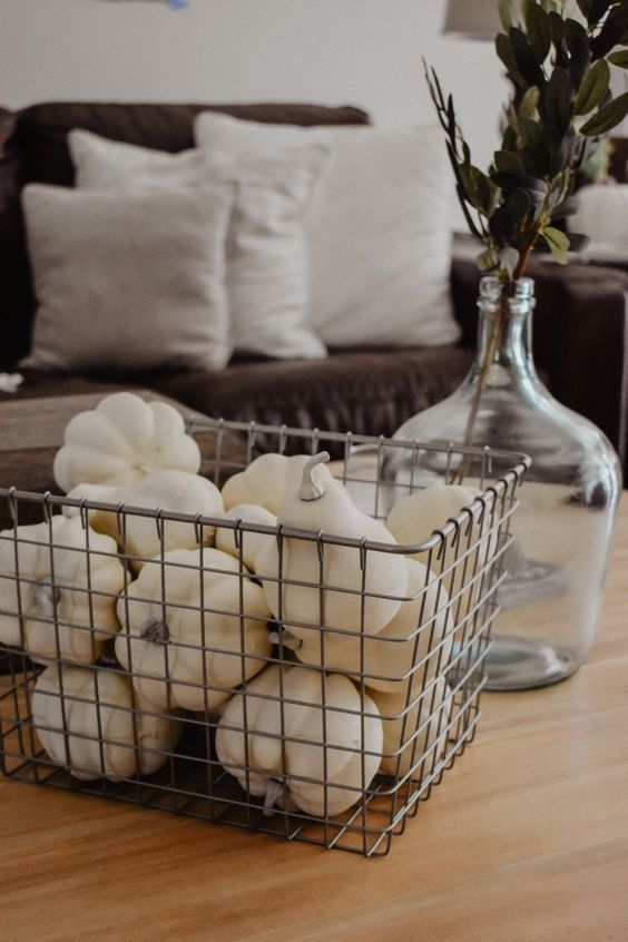 a wire box filled with faux white pumpkins and gourds and a clear vase with dried herbs