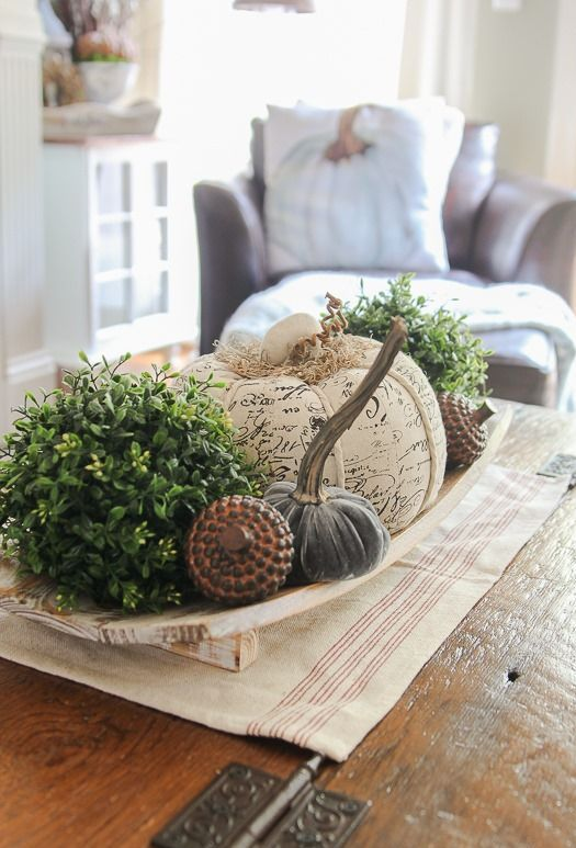 a wooden bowl with greenery balls, fabric pumpkins, fake acorns for a cool and bold famrhouse-inspired look