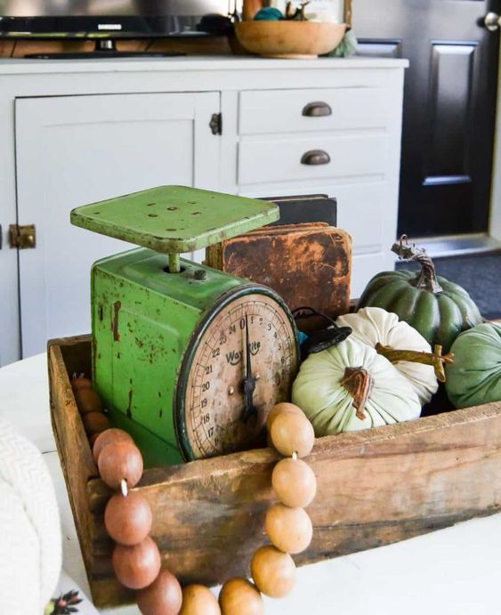 a wooden box with wooden beads, natural and fabric pumpkins and vintage scales for a rustic space