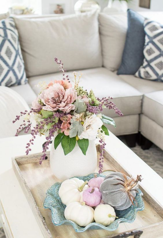 a wooden tray with a pastel floral arrangement plus leaves and a blue bowl with faux pumpkins in pastels