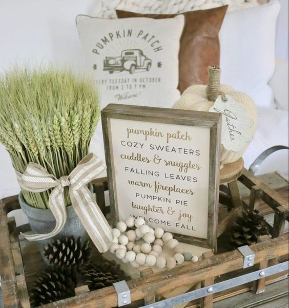 a wooden tray with beads, pinecones, wheat in a small bucket, fabric pumpkins and a sign for cozy fall decor