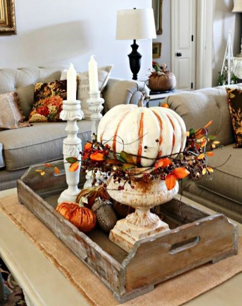 a wooden tray with orange fabric pumpkins, giant acorns and a large painted pumpkin with leaves and berries in an urn