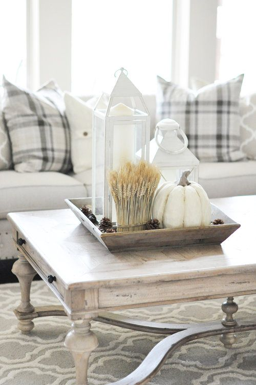 a wooden tray with wheat, white candle lanterns and a faux white pumpkin for fall living room decor