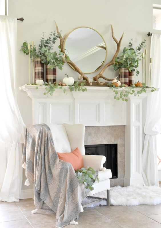 a woodland fall mantel with antlers, natural pumpkins, greenery and plaid vases