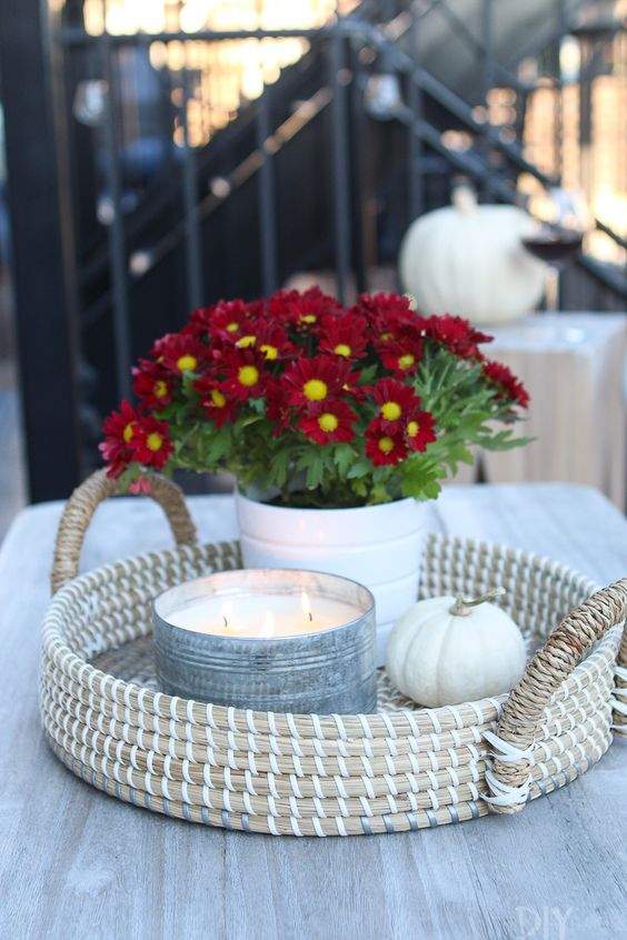 a woven tray with a white pumpkin, an oversized candle in a metal tin and pitted burgundy blooms for a chic and bold look