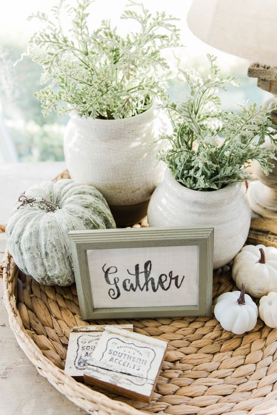 a woven tray with white and green pumpkins, a sign, potted greenery for famrhouse coffee table decor
