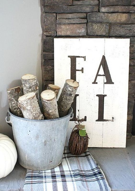 an aged metal bucket with large and thick branches or firewood and a vine pumpkin for fireplace decor