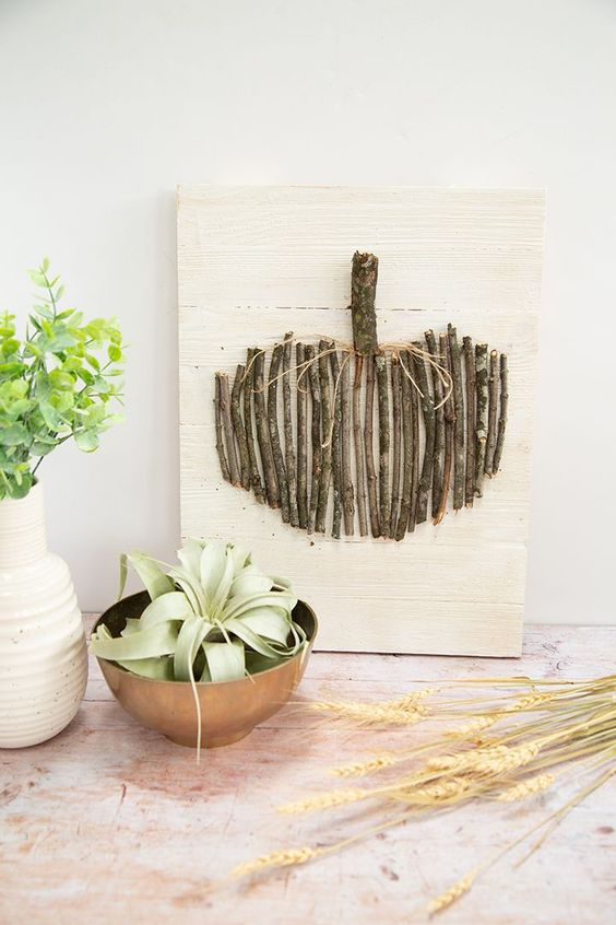 an artwork of a pumpkin done with twigs and branches is a cute DIY for this fall