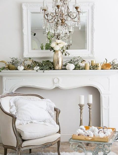 an elegant fall mantel decorated with fresh greenery, fabric and porcelain pumpkins and white roses in a metallic vase