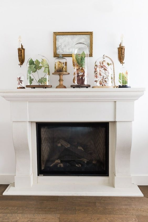 an elegant fall mantel with dried leaves and greenery in a variety of cloches