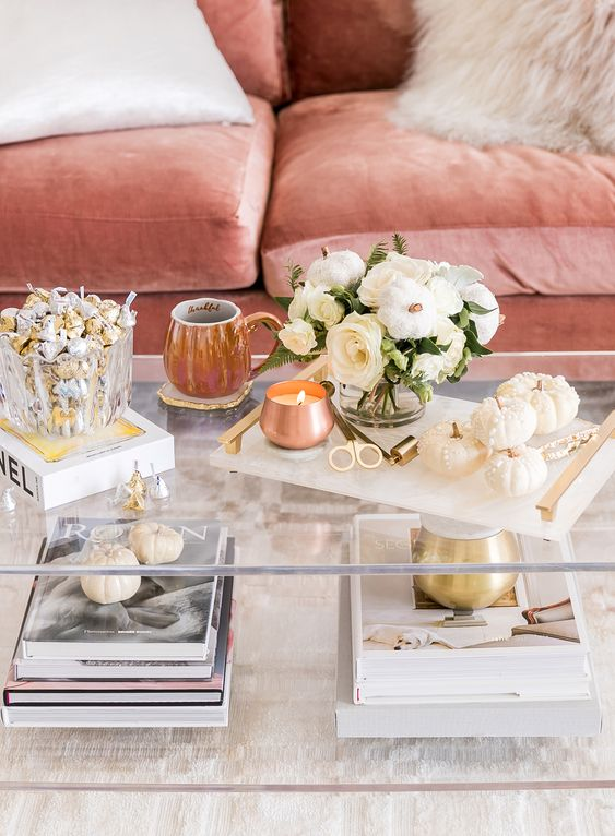 an elegant marble tray with a copper candle, a stack of embellished pumpkins and a white bloom arrangement with a pumpkin