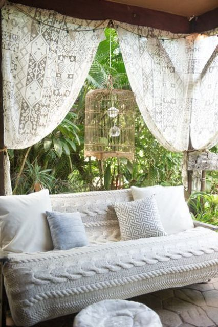 an outdoor sofa covered with a cool crochet patterned piece looks very cozy and very stylish