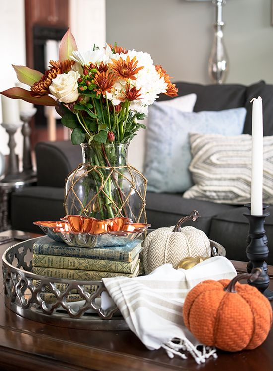fabric pumpkins, a clear vase with rust and white blooms and a stack of books for fall decor