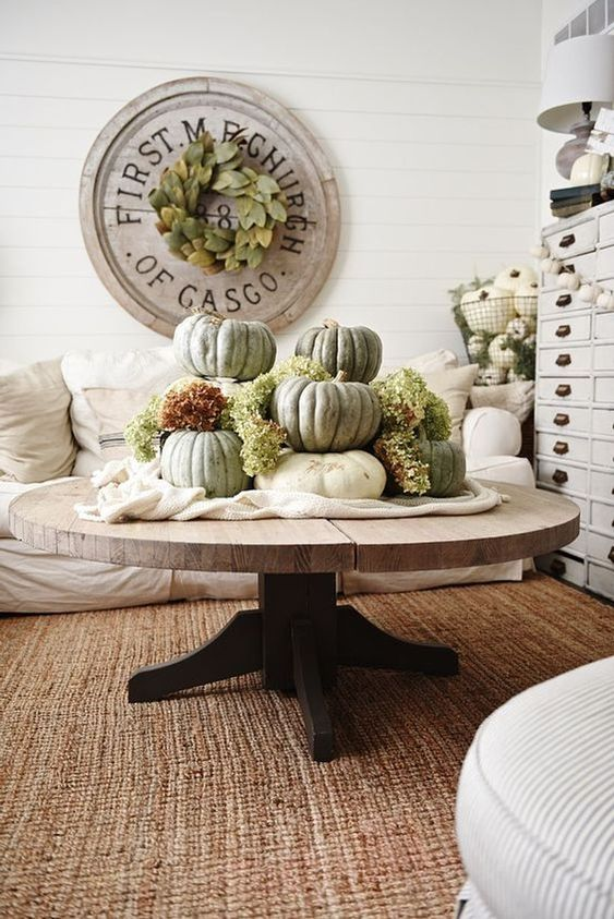 white fabric and large heirloom pumpkins plus green hydrangeas stacked on it for a famrhouse living room