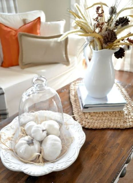 white pumpkins in a cloche and a white jug with dried blooms, leaves and wheat for cozy farmhouse living room decor