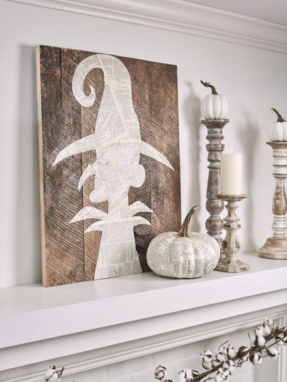 a Halloween mantel with a witch artwork, a white newspaper pumpkin and white candles and pumpkins on candleholders