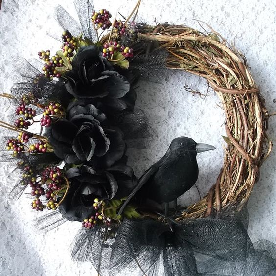 a Halloween rustic wreath of vine, with black blooms, berries and a crow is a refined and cool piece