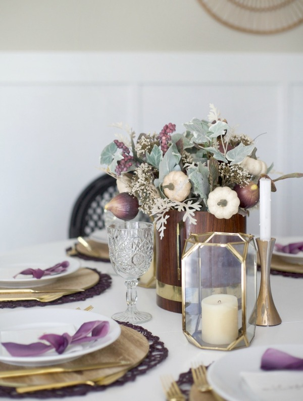 a Thanksgiving table setting with plywood placemats and a gold faceted candleholder, purple placemats and bows, purple veggies and berries