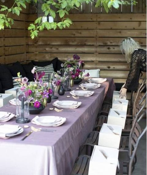 a Thanksgiving tablescape with a lilac tablecloth, bold purple and lilac blooms, black and gold vases and gold cutlery