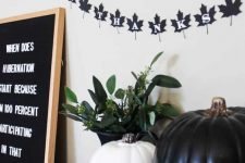 a black and white pumpkin, a black leaf bunting, a black sign and greenery in a black vase for chic and lovely Halloween decor