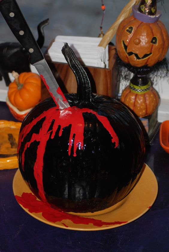 a black bloody pumpkin with a knife tucked in is a cool idea for Halloween party decor, whether it's a Dexter or some other one