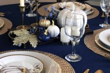 a bold Thanksgiving table with gold cutlery, woven chargers, printed plates, blue, gold and white pumpkins and candles