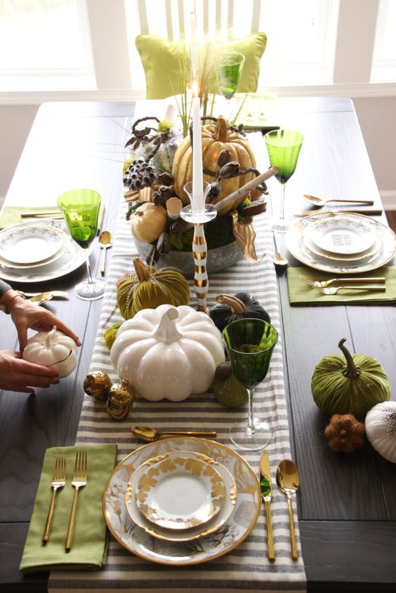 a bold Thanksgiving tablescape with a striped runner, green napkins and placemats, green glasses and faux pumpkins