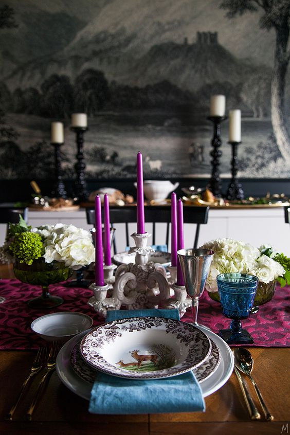 a bold and refined Thanksgiving tablescape with a purple table runner and candles, a blue napkin and glass, white blooms and greenery