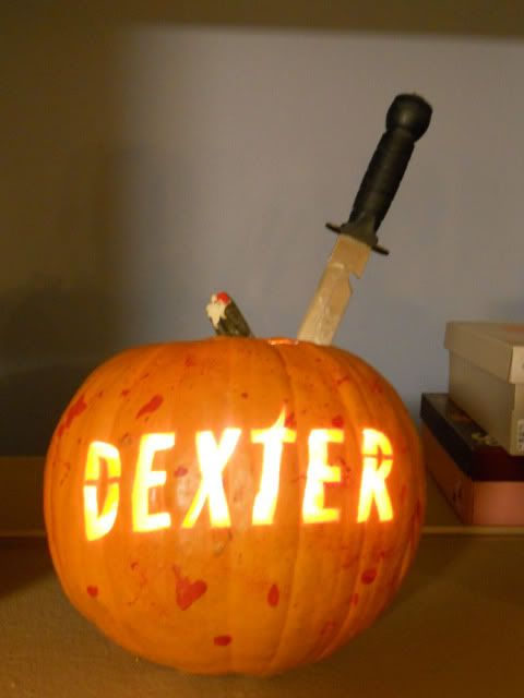 a bold lit up DEXTER pumpkin with blood splatters and a knife is a bold solution for a Dexter-themed party