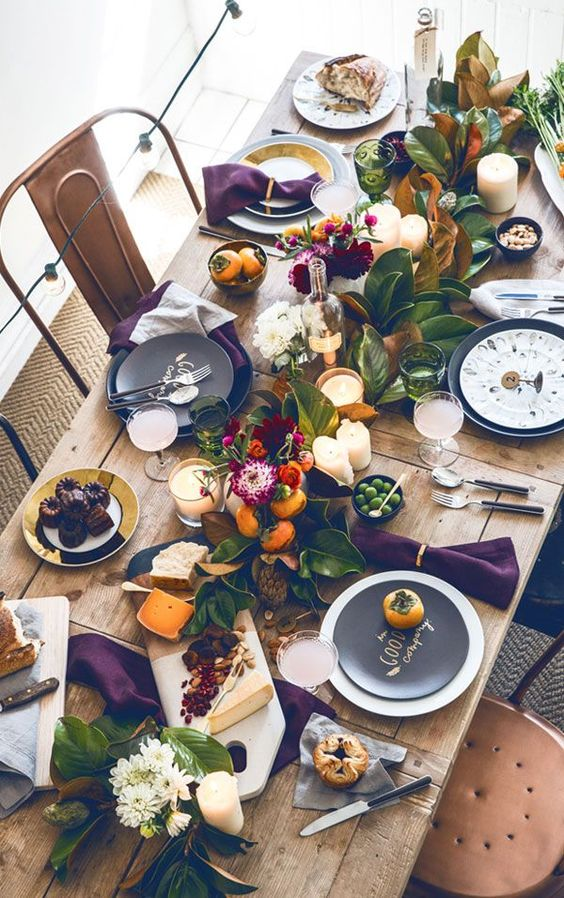 a bright Thanksgiving table setting with an uncovered table, a greenery and fruit runner, candles, blooms and black chargers
