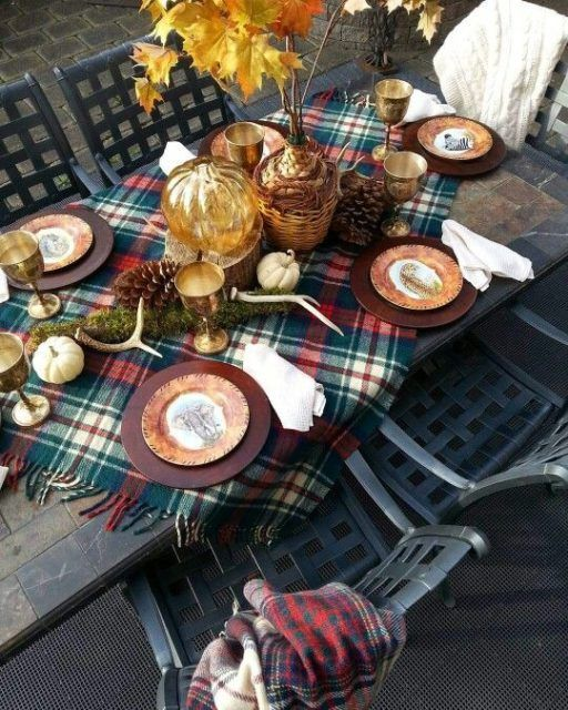 a bright Thanksgiving table with antlers, pumpkins, pinecones, a plaid tablecloth and a fall leaf arrangement