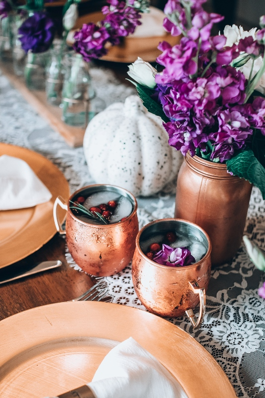 a bright Thanksgiving tablescape with a lace runner, bold purple blooms, spaeckled pumpkins, copper mugs and chargers