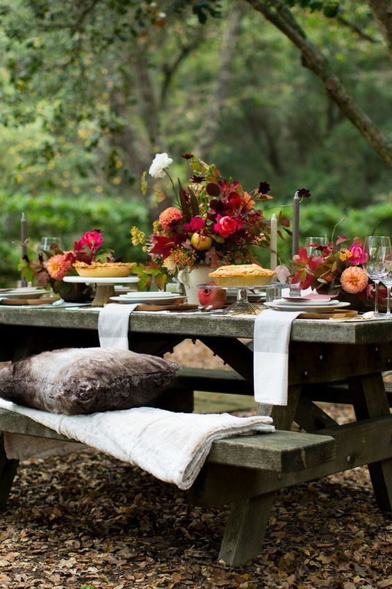 a bright and chic Thanksgiving table with bold florals, tall candles and some foliage plus neutral linens