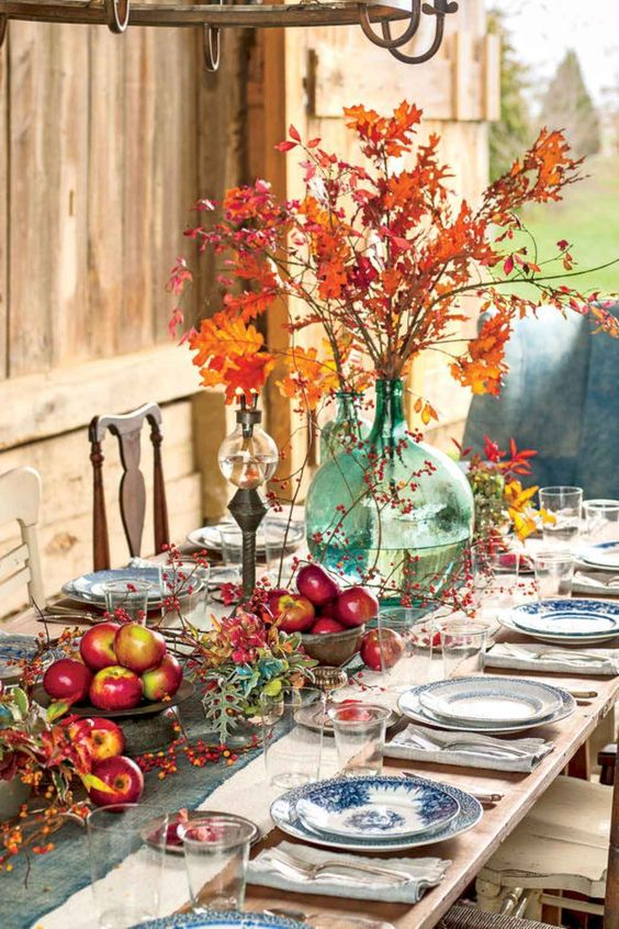 a bright and natural Thanksgiving tablescape with bold apple arrangements, berries, leaves and a bright fall leaf arrangement in a large vase