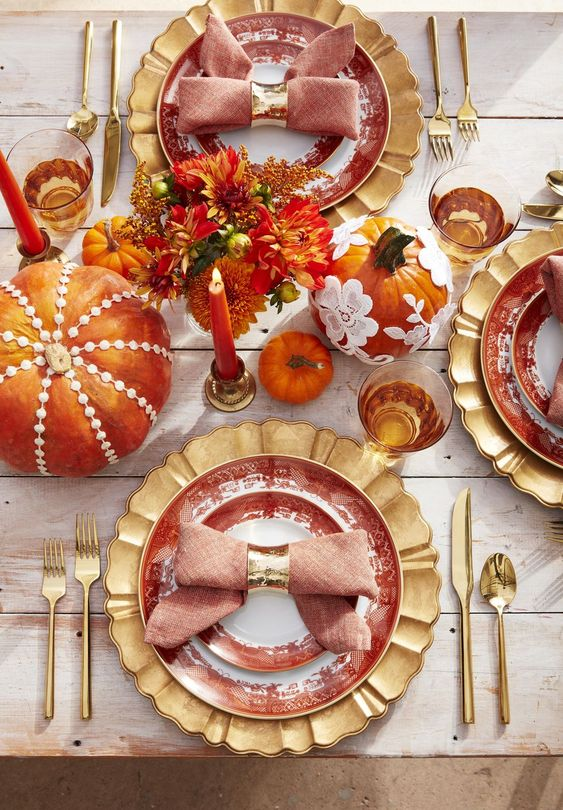 a bright and whisy Thanksgiving tablescape with gold chargers, cutlery, colorful pumpkins and floral arrangements, bold candles